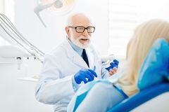 Cheerful dentist holding false teeth in hands. Detailed consultation. Professional dentist expressing cheer and holding false teeth in hands while the patient Royalty Free Stock Images