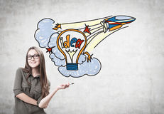 Cheerful designer with a marker, start up idea. Portrait of a smiling young woman wearing a khaki shirt and glasses and holding a marker. She is standing near a Royalty Free Stock Image