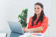 Cheerful designer working on her laptop Stock Images