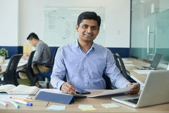 Cheerful developer. Smiling handsome Indian developer working at table in open space office stock photos