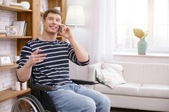 Cheerful differently abled man being high-spirited. Pleasant talk. Attractive male person keeping smile on his face and actively gesticulating while talking per Stock Images