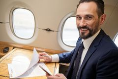 Cheerful diplomat working on plane board. Portrait of happy successful man in airplane working with documentation, he is looking at camera and laughing Stock Image