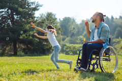 Cheerful disabled father and daughter playing with soap bubbles. Enjoying active weekend. Pleasant upbeat young men with disabilities sitting in the meadow and Stock Images