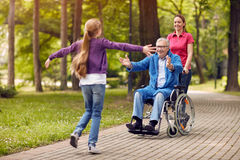 Cheerful disabled grandfather enjoying with his granddaughter an Royalty Free Stock Photos