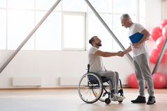 Cheerful disabled patient greeting his physical therapist in the gym. Nice to meet you. Happy positive smiling disabled men sitting in the wheelchair while stock image