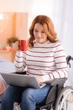 Cheerful disabled woman with her laptop Royalty Free Stock Photography
