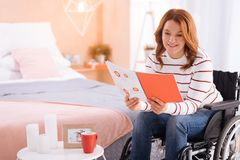 Cheerful disabled woman reading in the wheelchair Royalty Free Stock Image