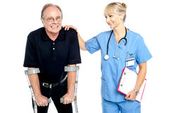 Cheerful doctor encouraging her patient to walk with crutches. Smiling faces Royalty Free Stock Images