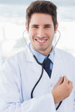 Cheerful doctor with his stethoscope looking at camera Royalty Free Stock Image