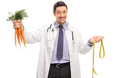 Cheerful doctor holding a bunch of carrots Stock Image