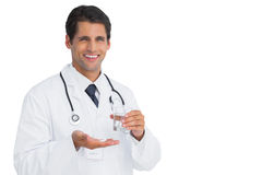 Cheerful doctor holding tablets and water Stock Photography