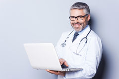 Cheerful doctor with laptop. Stock Images