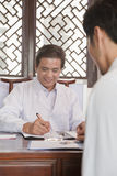 Cheerful Doctor Meeting with a Patient, writing notes Royalty Free Stock Photos