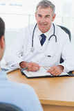 Cheerful doctor prescribing drug to his patient Royalty Free Stock Photos