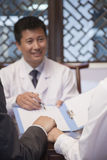 Cheerful Doctor Presents Results to Patient Stock Photo