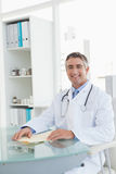 Cheerful doctor sitting at his desk Royalty Free Stock Photography