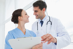 Cheerful doctor and surgeon looking at each other Royalty Free Stock Images