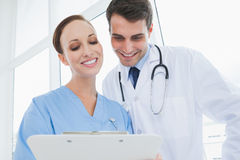 Cheerful doctor and surgeon viewing documents together Royalty Free Stock Photos