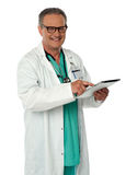 Cheerful doctor using wireless tablet device Stock Photo