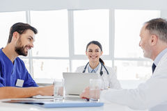 Cheerful doctors discussing human health with satisfaction Royalty Free Stock Images