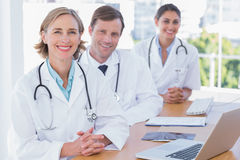 Cheerful doctors posing at their desk Royalty Free Stock Photos