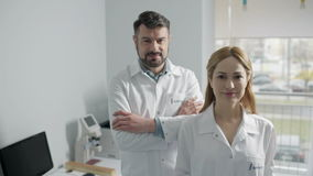 Cheerful doctors standing in office. Always at your service. Two young medical professionals in white overalls smiling while standing at the office stock footage