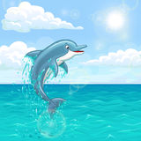 Cheerful dolphin in summer sea. The dolphin who is jumping out of sea water of the ocean in splashes against the blue sky and the sun. Landscape of summer mood Stock Image