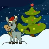 Cheerful donkey in a Christmas hat, snow and a smart Christmas t. Ree Stock Images