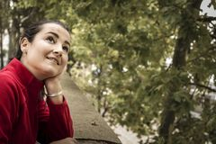 Cheerful dreamy woman. Side view of cheerful dreamy woman leaning on handrail and looking at trees Stock Image