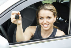 Cheerful driver. Woman in car showing the keys Royalty Free Stock Photo