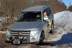 Cheerful driver pulls car out of hole with winch Royalty Free Stock Images