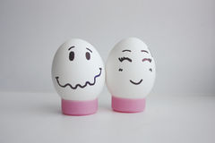 Cheerful eggs of shyness shyness. Cheerful eggs with two face on white background on stand concept of embarrassed shyness.Photo for your design Stock Images