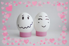 Cheerful eggs of shyness shyness. Cheerful eggs with two face on white background on stand concept of embarrassed shyness.Photo for your design Frame of hearts Royalty Free Stock Images