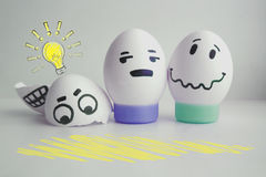 Cheerful eggs with two face concept warned. Concept of idea. Light. Cheerful eggs with two face on white background on stand concept warned. Photo for your royalty free stock photography