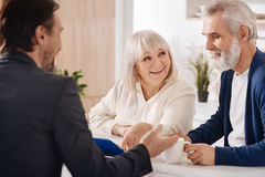 Cheerful elderly couple discussing contract at home. Ready for signing. Delighted upbeat elderly couple sitting at home and having conversation with advisor stock photos