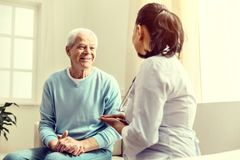 Cheerful elderly gentleman consulting with nurse. Staying positive. Selective focus on a happy retired men beaming while sitting next to his doctor and talking royalty free stock photo