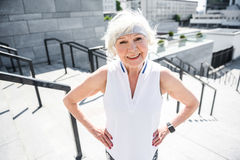 Cheerful elderly lady exercising on big city ladder outdoor Royalty Free Stock Images