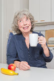 Cheerful elderly lady with mug. Apple and banana Stock Photography