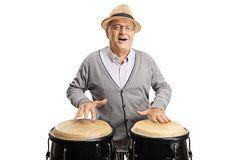 Cheerful elderly man playing conga drums stock images
