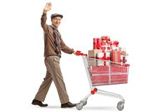 Cheerful elderly man with a shopping cart full of presents waving at the camera. Full length shot of a cheerful elderly man with a shopping cart full of presents stock photography