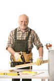 Cheerful elderly man tinkering stock photo