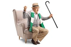 Cheerful elderly sports fan with a cane and a scarf sitting in an armchair royalty free stock photography
