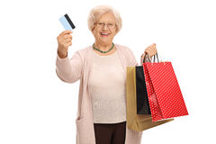 Cheerful elderly woman with a credit card and shopping bags Royalty Free Stock Photo