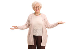 Cheerful elderly woman gesturing with her hands. And looking at the camera isolated on white background Royalty Free Stock Image