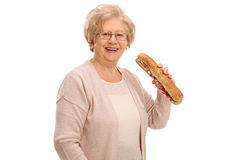 Cheerful elderly woman having a sandwich Stock Images
