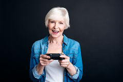 Cheerful elderly woman holdign game console Stock Images