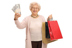 Cheerful elderly woman holding stacks of money and shopping bags Royalty Free Stock Photo