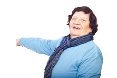 Cheerful elderly woman pointing to copy space Stock Photo