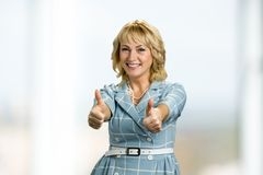 Cheerful elderly woman showing thumbs up sign. Stock Image