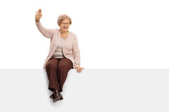 Cheerful elderly woman sitting on a panel and waving Stock Image